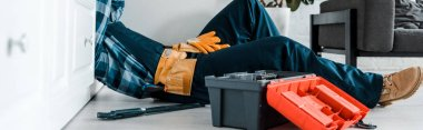 panoramic shot of handyman working in kitchen near toolbox while lying on floor