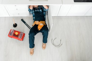 Top view of handyman lying on floor near toolbox stock vector
