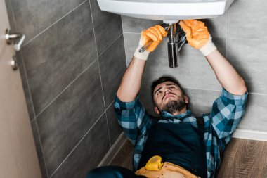 selective focus of repairman fixing water damage with wrench in bathroom