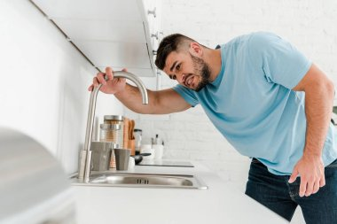selective focus of stressed man looking at sink in modern kitchen