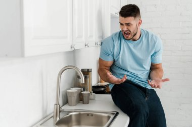 upset man gesturing and screaming near faucet in kitchen