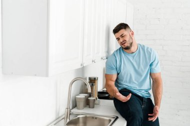 selective focus of upset man looking at faucet and sink in kitchen