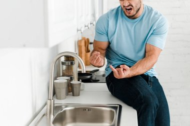 cropped view of upset man showing middle fingers and screaming near faucet in kitchen