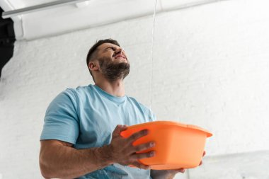 bearded man with closed eyes holding plastic wash bowl near pouring water