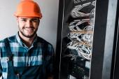 Glücklicher Techniker blickt auf Kamera in der Nähe von Kabeln und Leitungen
