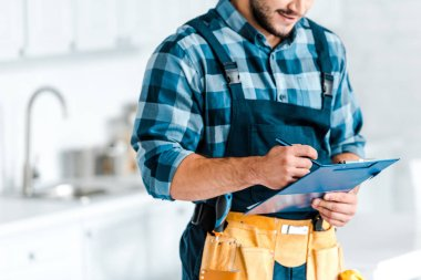 Cropped view of of bearded workman holding clipboard and pen stock vector