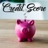 Photo toy piggy bank on wooden desk near credit score lettering in office