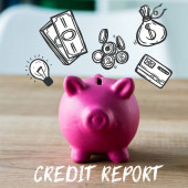 Photo toy piggy bank on wooden desk near credit report lettering in office