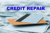 selective focus of pile with credit cards near credit repair lettering on dollar banknotes