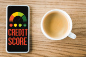 top view of smartphone with credit score lettering on screen near cup of coffee on table