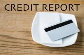 kreditní karta na desce s příjmový a kreditní zprávou na dřevěném stole