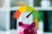 Fotografie pink piggy bank on wooden desk near colorful speed meter with letters in office