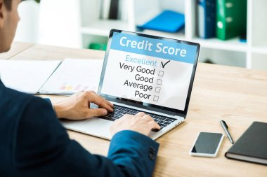 selective focus of man typing on laptop with credit score lettering near smartphone with blank screen on table