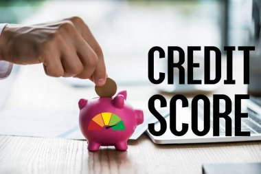 cropped view of businessman putting coin into pink piggy bank near credit score lettering and laptop