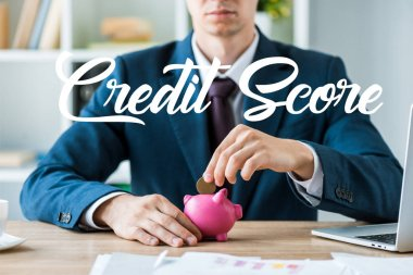 Cropped view of businessman putting metallic coin into pink piggy bank near credit score letters stock vector