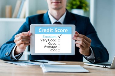 selective focus of happy man holding digital tablet with credit score letters in office