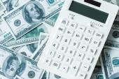 Nejlepší pohled na bílou kalkulačku na dolarových bankovkách