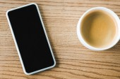 Ansicht des Smartphones von oben mit leerem Bildschirm in der Nähe der Tasse Kaffee