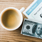 top view of cup with coffee near paper with credit report lettering on paper and money