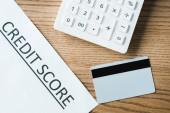 pohled na kreditní kartu v blízkosti papíru s písmem s kreditními skóre a kalkulačkou