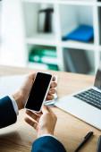 Fényképek levágott kilátás-ból ember tárolás Smartphone-val üres képernyő mellett laptop-ra asztal