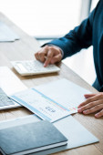 selective focus of businessman holding paper with credit report lettering and counting on calculator