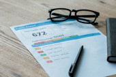 selective focus of glasses near document with credit report letters