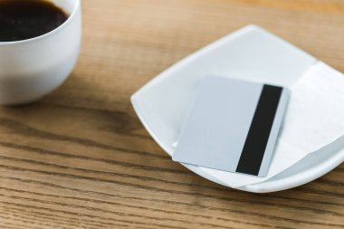 credit card in white plate with receipt near cup with coffee on wooden table
