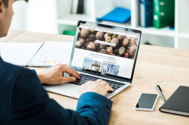 KYIV, UKRAINE - JULY 8, 2019: man typing on laptop with depositphotos website near smartphone with blank screen on table stock vector