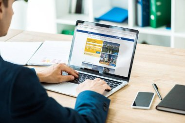 KYIV, UKRAINE - JULY 8, 2019: man typing on laptop with booking website near smartphone with blank screen on table stock vector