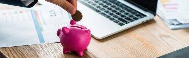 Panoramic shot of businessman putting coin into pink piggy bank near laptop stock vector