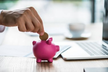 cropped view of businessman putting coin into pink piggy bank near laptop