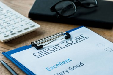 selective focus of paper with credit score lettering near glasses
