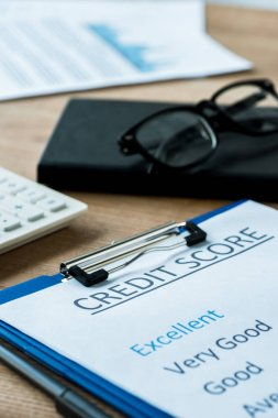 selective focus of paper with credit score lettering near glasses and calculator
