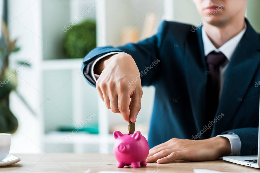 Cropped view of businessman putting metallic coin into piggy bank near laptop stock vector