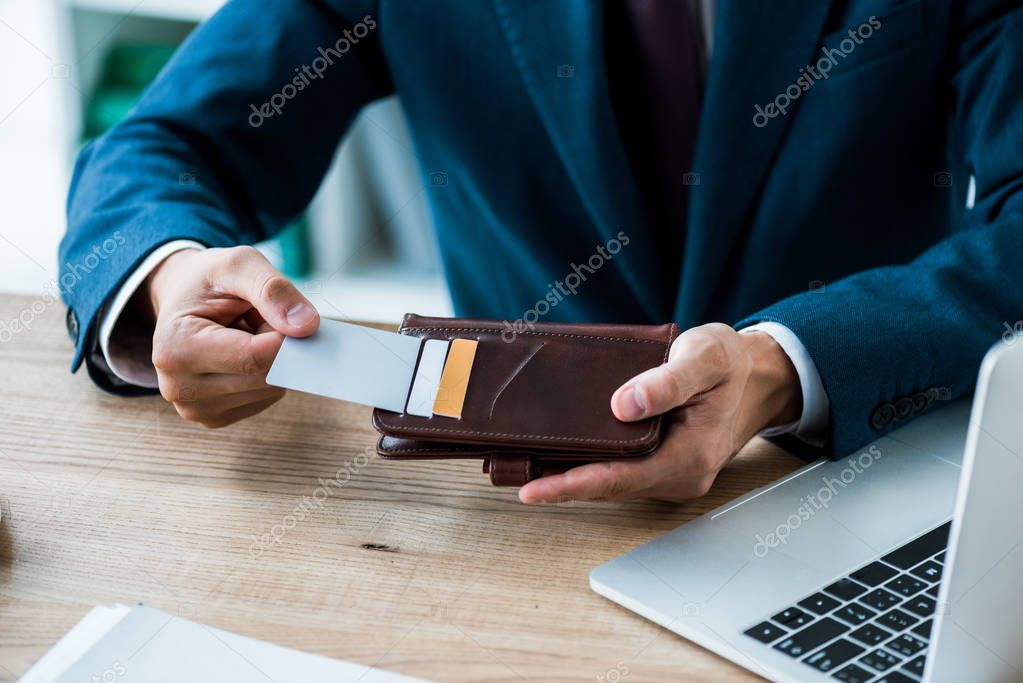 Cropped view of man taking credit card while holding black wallet near laptop stock vector