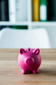 pink toy piggy bank on wooden desk in office