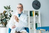 vousatý doktor ve skleničkách a bílém plášti, držící na klinice model páteře