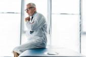 zamyšlený lékař v brýlích a bílém plášti, který sedí na masážním stolku a dotýká se obličeje
