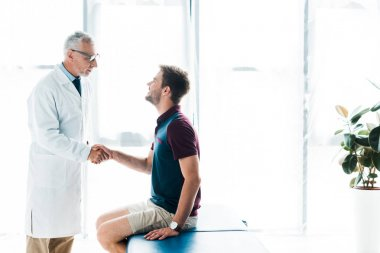 Doctor in glasses shaking hands with happy man in clinic stock vector