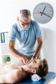 vousatý chiropraktik, masáž muže s bolestí na masážním stole