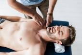 vista dallalto del chiropratico facendo massaggio alluomo con dolore