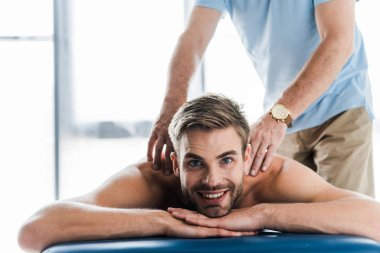 cropped view of chiropractor doing massage to positive patient on massage table