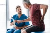 selektivní zaměření lékaře s modelem páteře a s pohledem na pacienta gestikulovat při dotyku se zády