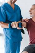 Fotografia vista cropped di medico felice in piedi vicino uomo maturo esercizio con manubrio in clinica