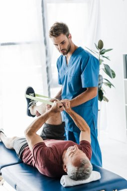 handsome doctor holding leg of mature patient exercising with elastics