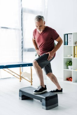 middle aged man exercising on step platform in clinic