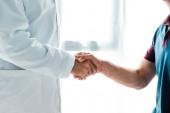 Ausgeschnittene Ansicht eines Arztes im weißen Mantel, der einem Mann die Hand schüttelt