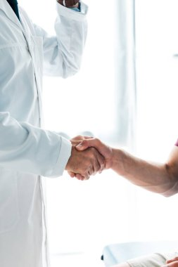 Cropped view of doctor in white coat shaking hands with patient stock vector