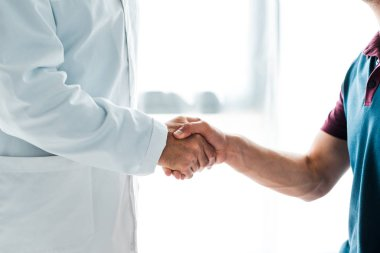Cropped view of doctor in white coat shaking hands with man stock vector